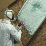 Applying spray foam insulation.